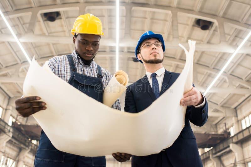 Bauunternehmer, die Plan des Gebäudes besprechen stockfoto