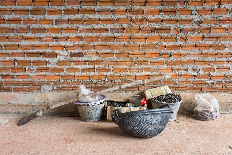 Bauwerkzeuge setzten an konkreten Boden nahe Backsteinmauer unter c stockfotos