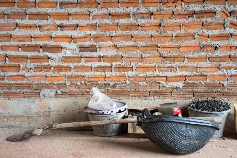 Bauwerkzeuge setzten an konkreten Boden nahe Backsteinmauer unter c stockbilder