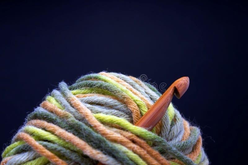 Bavardez la boule de laine, photo en bambou naturelle en bois de crochet de crochet sur le fond foncé Vue de face, foyer mou séle image libre de droits