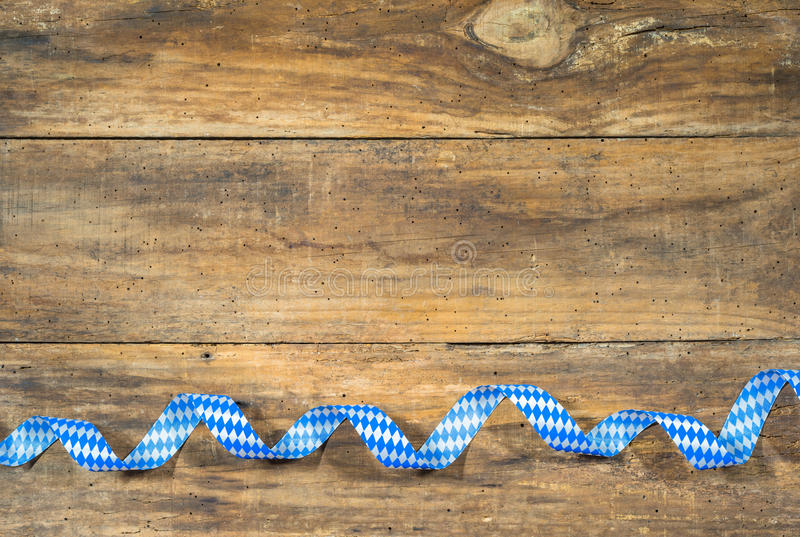 Bavaria or Oktoberfest Background with traditional blue white colors ribbon on rustic wood. stock photography