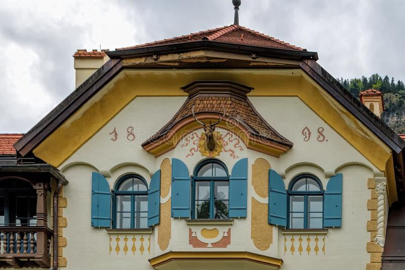 Bavarian architecture of Hohenschwangau village. Facade part of Museum of the Bavarian Kings building with the deer head with. HOHENSCHWANGAU, GERMANY - Jun 10 royalty free stock photography