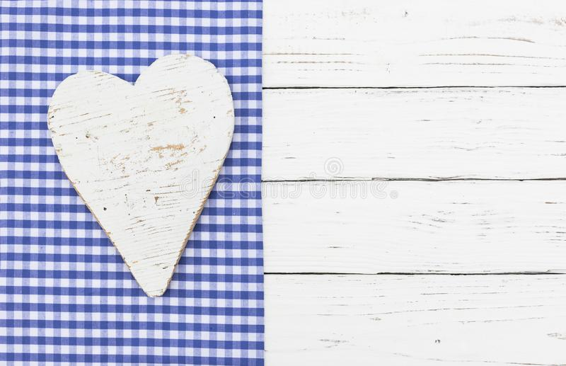 Bavarian background with white wooden heart on blue checked fabric border and white wood royalty free stock photo