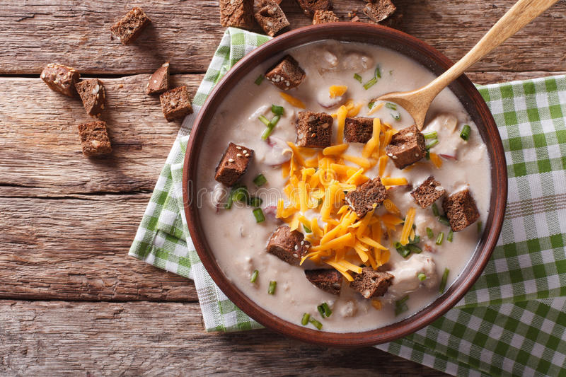 Bavarian beer soup with cheese and bacon close up in a bowl. horizontal top view. Bavarian beer soup with cheese and bacon close up in a bowl on the table stock photo