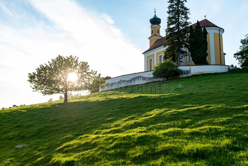 Bavarian church on an hill with an outshined tree stock image