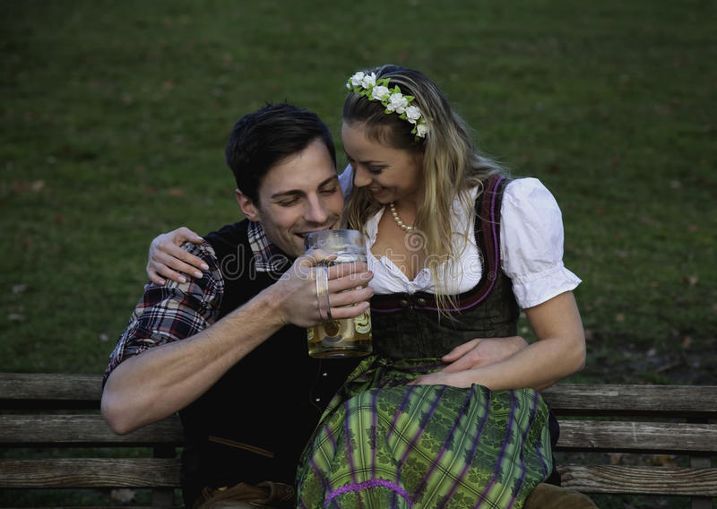 Bavarian Couple with Beer. Bavarian couple on a bench drinking beer