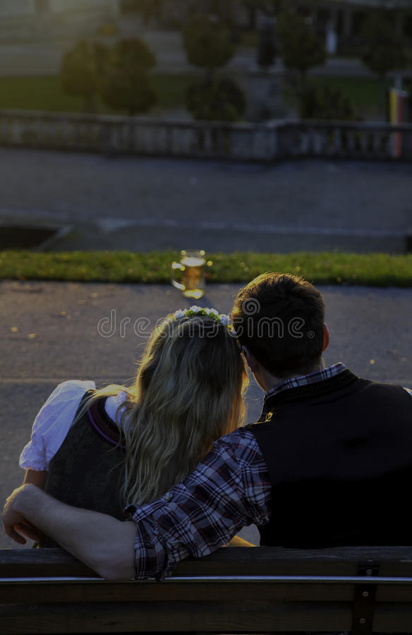 Bavarian Couple with Beer. Bavarian Couple relaxing on a bench