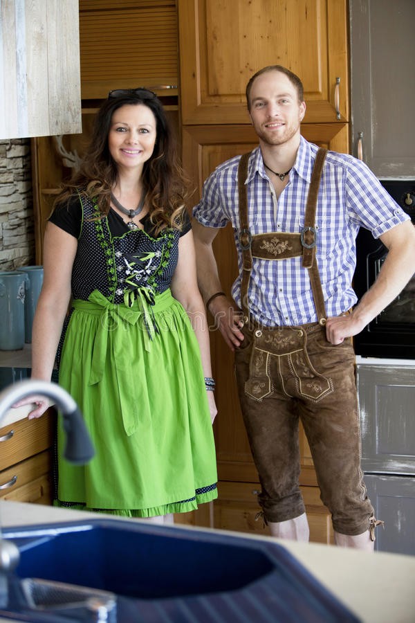 Bavarian couple standing in kitchen and smiling stock image