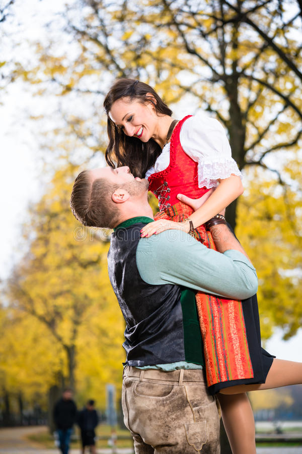 Bavarian couple in Tracht in loving embrace with uplift. Southern German couple in Tracht in loving embrace, he is lifting her up royalty free stock photo