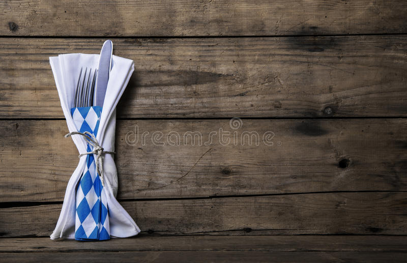Bavarian food. Old wooden background with knife and fork. Table. Old wooden background with knife and fork. Table decoration with blue and white checked napkin royalty free stock photography