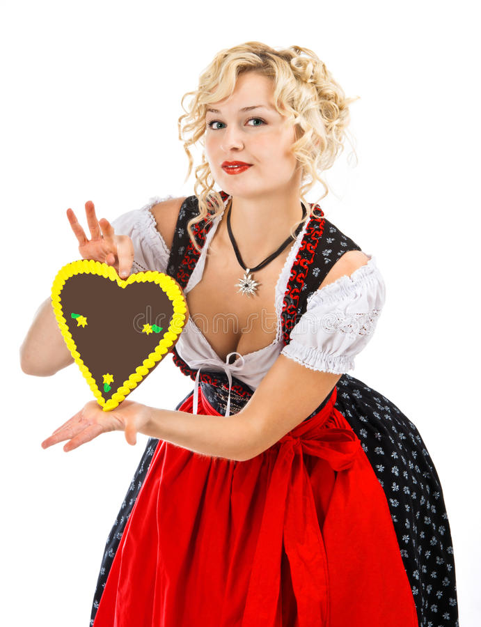 Bavarian girl in dirndl with octoberfest cookie. German bavarian girl in dirndl with typical octoberfest cookie royalty free stock photo