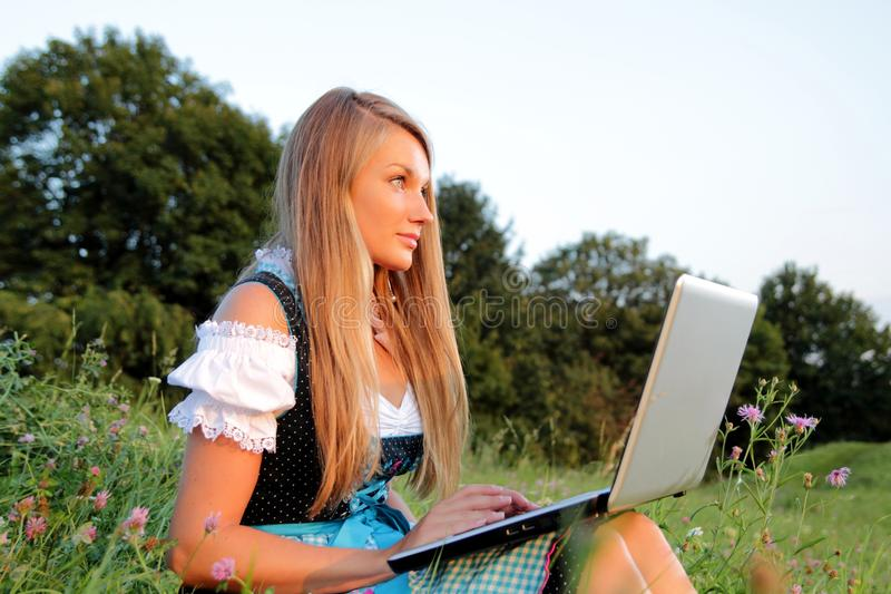 Bavarian Girl with Laptop in a flowering meadow