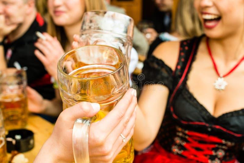 Bavarian girls drinking beer royalty free stock photo