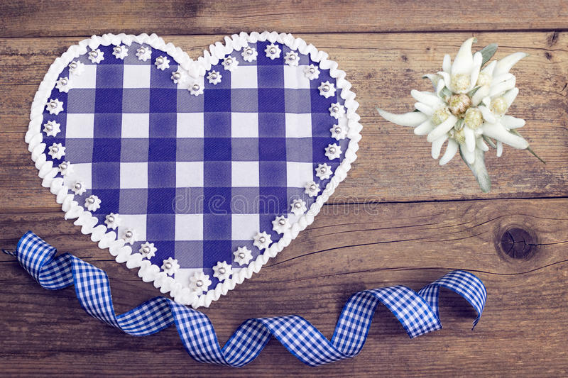 Bavarian heart with Edelweiss. Bavarian heart on wooden background with Edelweiss stock photos