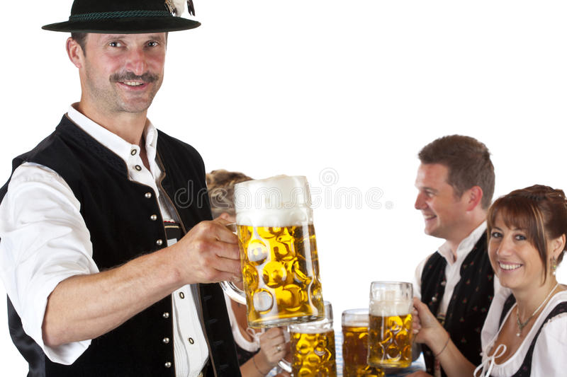 Bavarian man with friends drinks Oktoberfest beer royalty free stock photos