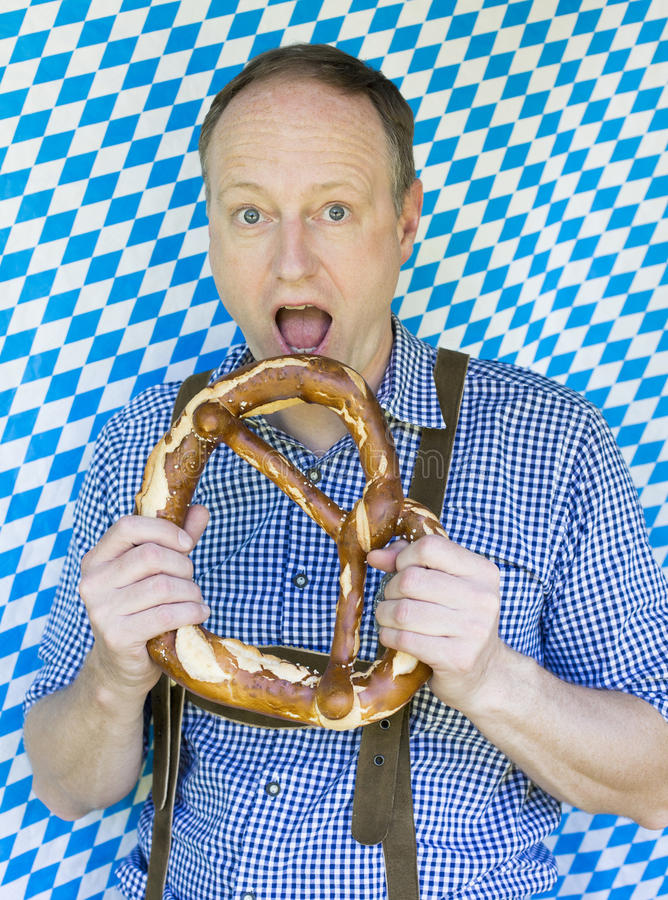 Bavarian man. Portrait of a bavarian man eating a giant pretzel stock images