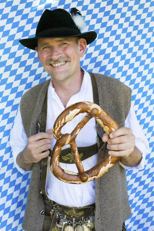 Bavarian man. Portrait of a bavarian man holding a giant pretzel royalty free stock images