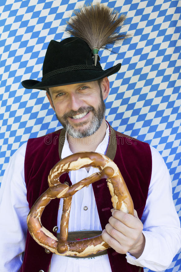 Bavarian man. Portrait of a bavarian man holding a giant pretzel royalty free stock photography