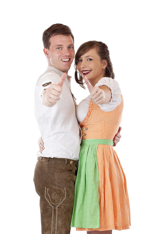 Bavarian man and woman with dirndl showing thumbs royalty free stock images