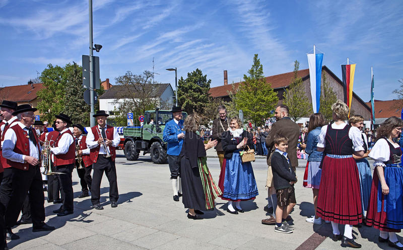 Bavarian May 1st festival. Garching, Germany - People with the traditional Bavarian costumes and the brass band wait the new may pole, to be erected in the main stock photo