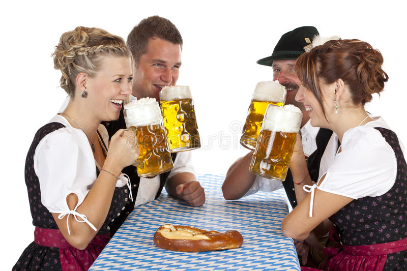 Bavarian men and women drinking Oktoberfest beer. Bavarian men and women drink cheerfully Oktoberfest beer stein. Isolated on white background stock photography