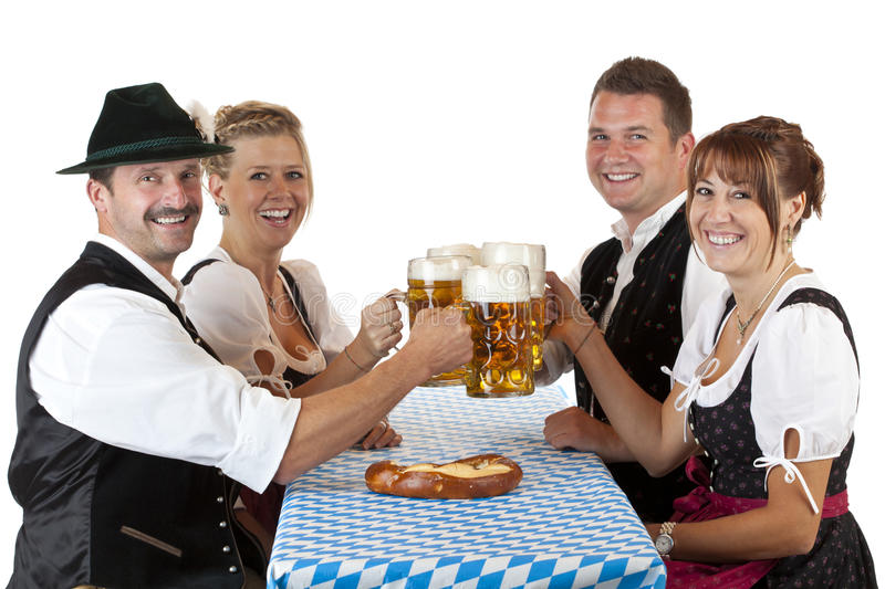 Bavarian men and women with Oktoberfest beer. Bavarian men and women toast with Oktoberfest beer stein. Isolated on white background stock photo