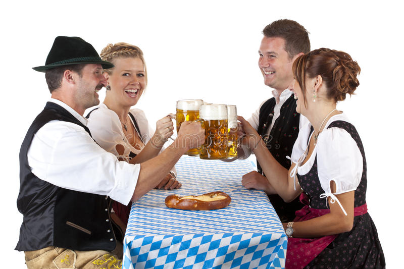 Bavarian men and women toast with beer stein. Bavarian men and women toast with Oktoberfest beer stein. Isolated on white background royalty free stock photos