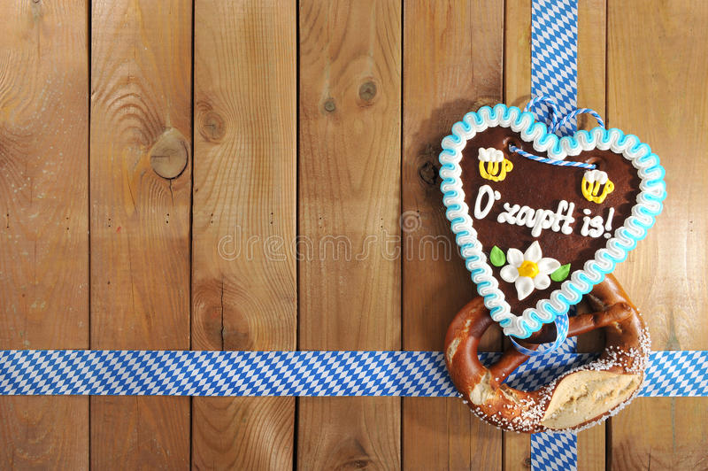 Bavarian Oktoberfest gingerbread heart. The beer is tapped - original bavarian salted soft pretzel and Oktoberfest gingerbread heart from Germany in front of royalty free stock photo