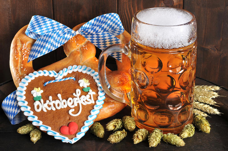 Bavarian Oktoberfest soft pretzel with beer. Original bavarian Oktoberfest big soft pretzel with beer mug, hops and gingerbread heart from Germany on old beer stock photography
