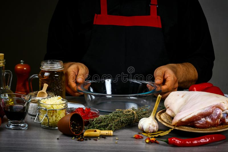 Bavarian pork knuckle with sauerkraut, sharp chili sauce and beer in cooking process preparing food. cooking recipe.  royalty free stock image