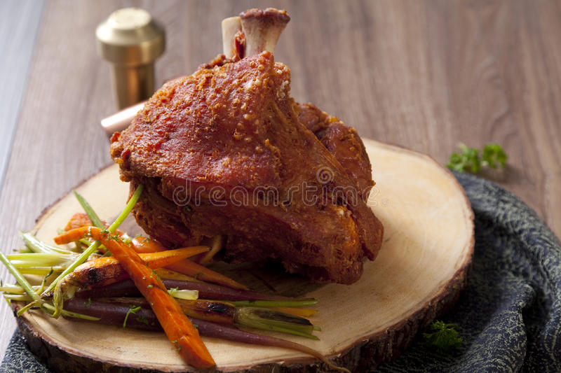 Bavarian roast pork knuckle. On wooden plate royalty free stock photography