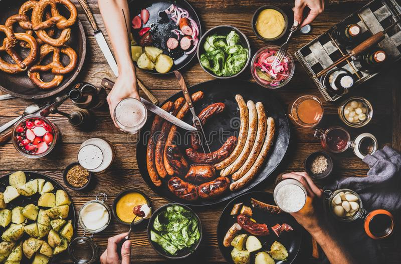 Bavarian sausages, snacks, sauces and beers for Octoberfest dinner party. Flat-lay of Octoberfest dinner table concept with grilled sausages, pretzel pastry royalty free stock image