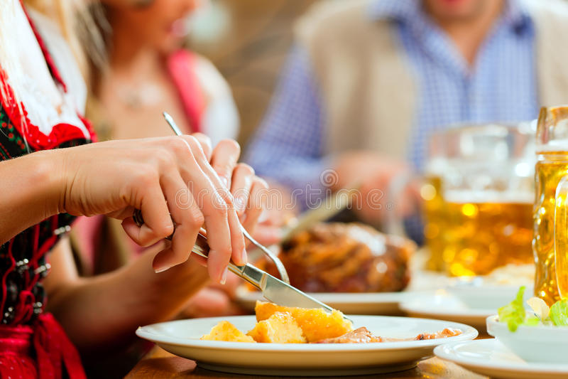bavarian som äter stek för folkporkrestaurang royaltyfria bilder