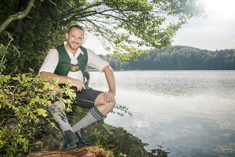 Bavarian tradition man at the lake stock image