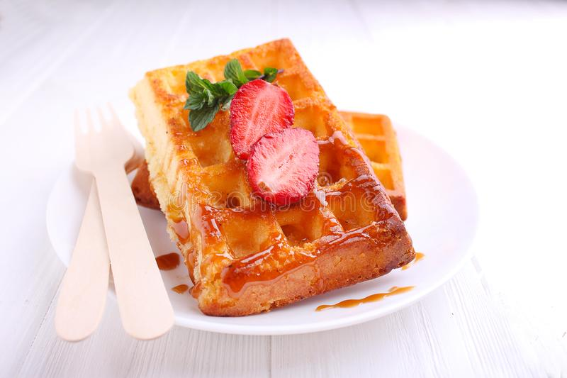 Bavarian waffles served with caramel and strawberry stock images