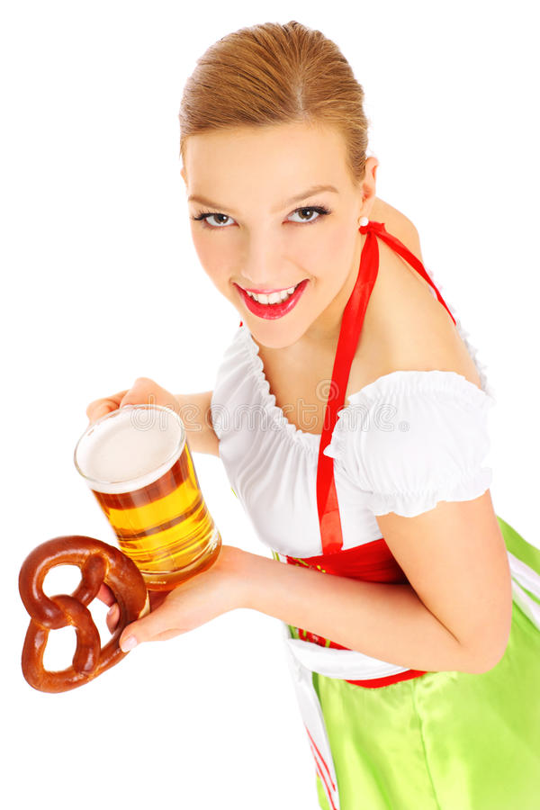 Bavarian waitress. A picture of a beautiful bavarian waitress holding a beer and a pretzel over white background stock photo
