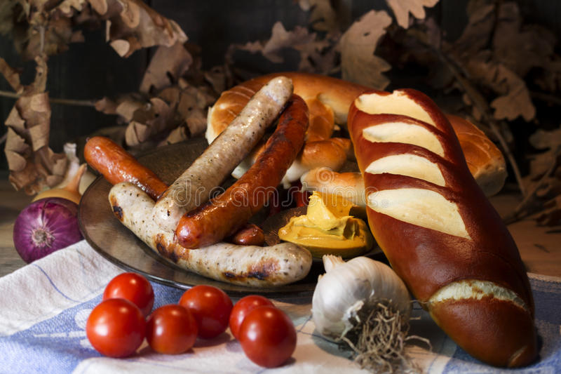 Bavarian White And Red Sausages With Mustard, Bavarian Buns and. Pretzels At The Table. October Fest Concept stock photography
