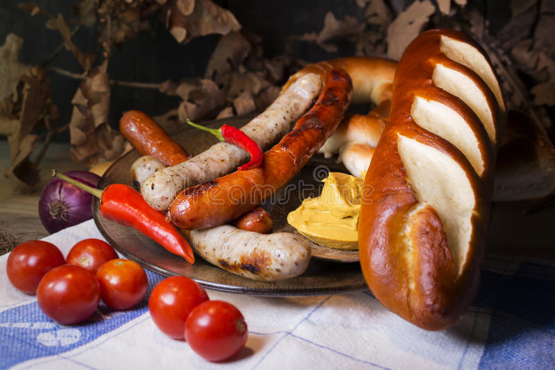Bavarian White And Red Sausages With Mustard, Bavarian Buns and. Pretzels At The Table. October Fest Concept royalty free stock image