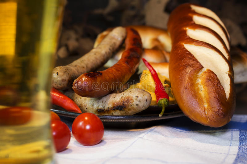 Bavarian White And Red Sausages With Mustard, Bavarian Buns and. Pretzels At The Table. October Fest Concept stock photo