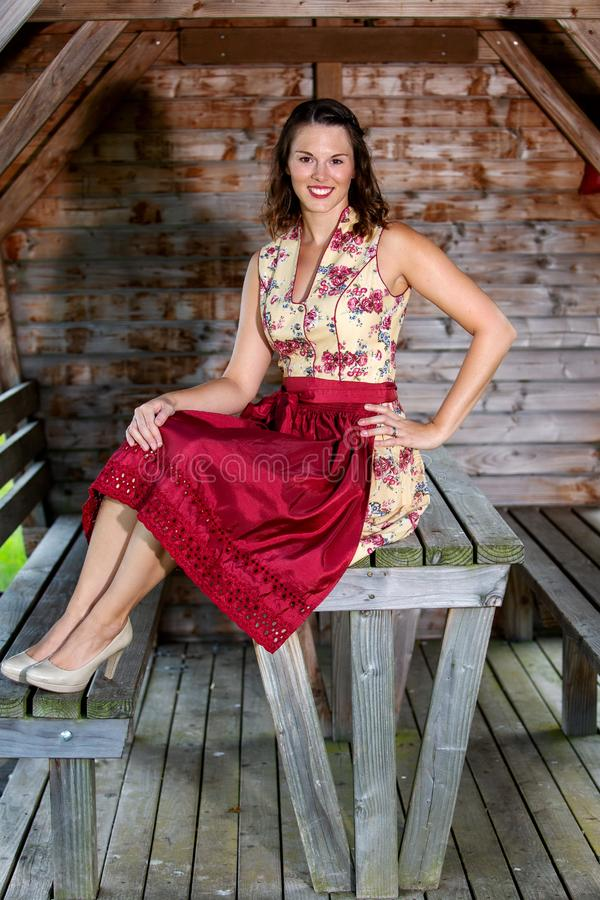 Bavarian woman in dirndl sitting in a hut royalty free stock photography
