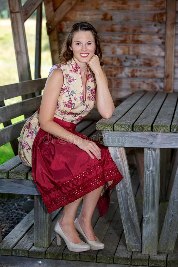 Bavarian woman in dirndl sitting in a hut royalty free stock photo