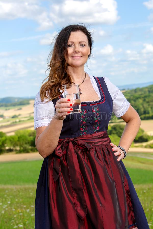 Bavarian woman in dirndl standing in meadow with glass of water royalty free stock photos