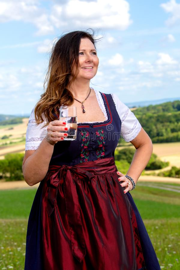 Bavarian woman in dirndl standing in meadow with glass of water stock photography
