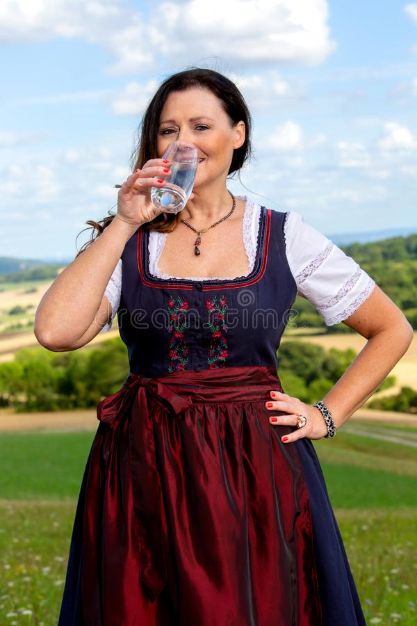 Bavarian woman in dirndl standing in meadow with glass of water royalty free stock image