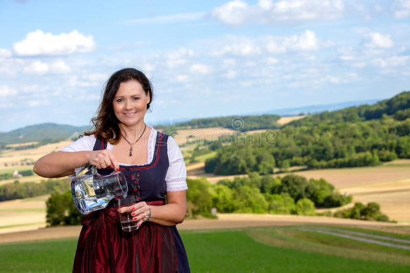 Bavarian woman in dirndl standing in meadow with glass of water royalty free stock images