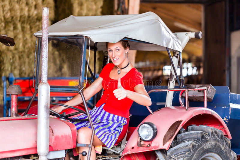 Bavarian woman with dress driving tractor. Bavarian woman with Dirndl dress driving tractor royalty free stock images