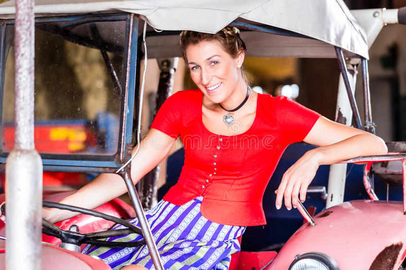 Bavarian woman with dress driving tractor royalty free stock photo