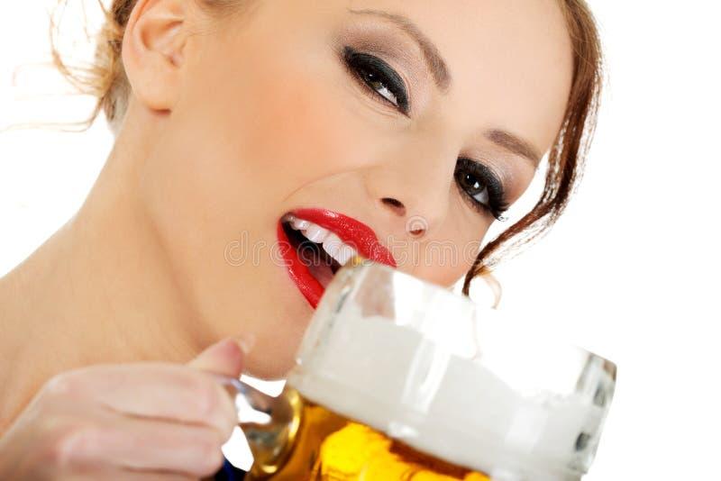 Bavarian woman drinking beer. Beautiful bavarian woman drinking beer stock image