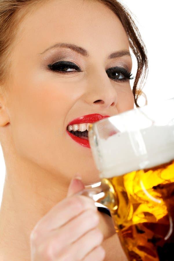 Bavarian woman drinking beer. Beautiful bavarian woman drinking beer royalty free stock photos
