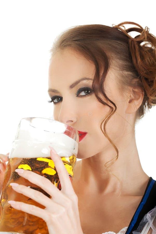 Bavarian woman drinking beer. Beautiful bavarian woman drinking beer royalty free stock images